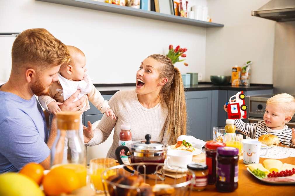 Eltern mit Baby und Kleinkind am Frühstückstisch
