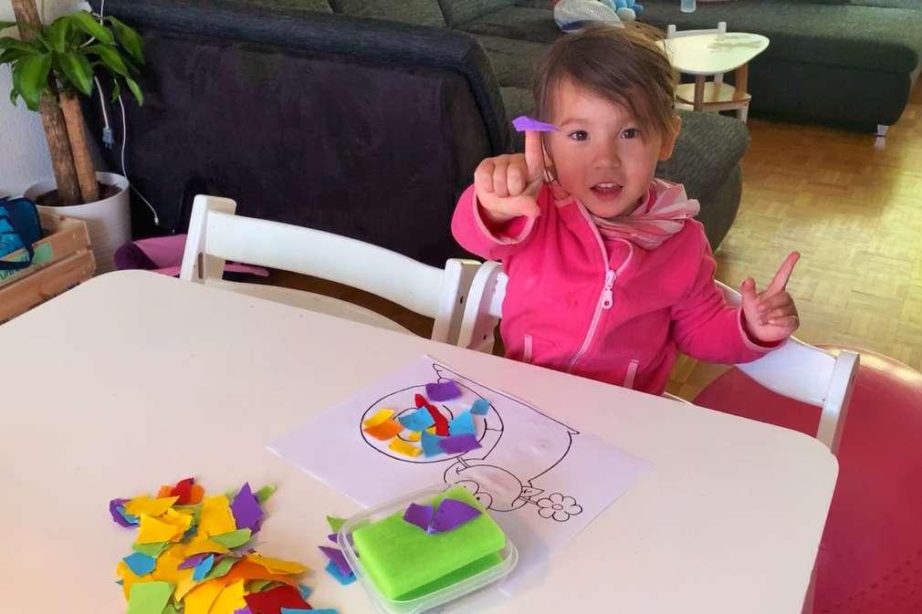 Kind bastelt ein Schnipselbild mit Schneckenmotiv