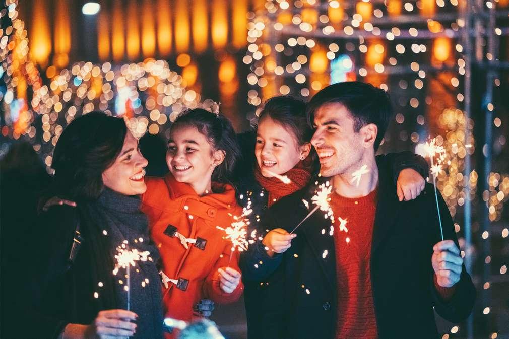 Eltern mit Kindern feiern draußen Silvester mit Wunderkerzen