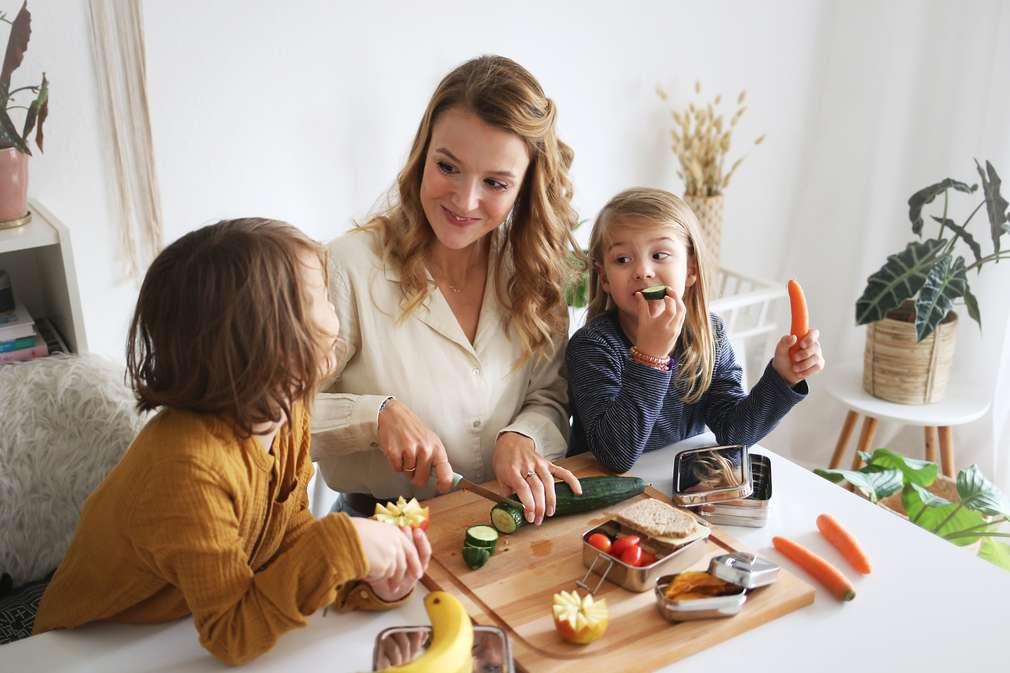 Mutter schneidet Gemüse und sitzt mit Sohn und Tochter am Tisch