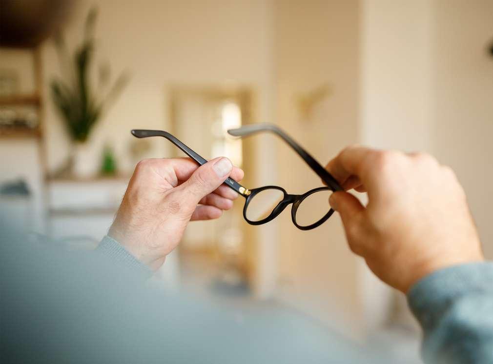 Mann der seine Brille abgenommen hat und in den Händen hält