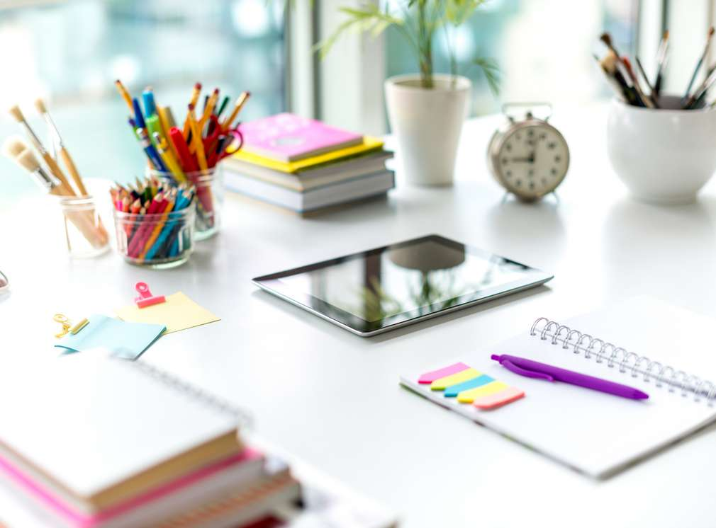 Schreibtisch mit georndeten Schreibutensilien wie Block, Tablet, Stifte und Wecker
