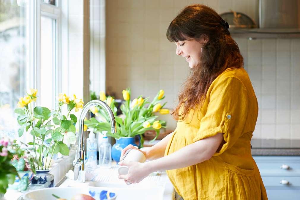 Schwangere Frau beim Abspülen