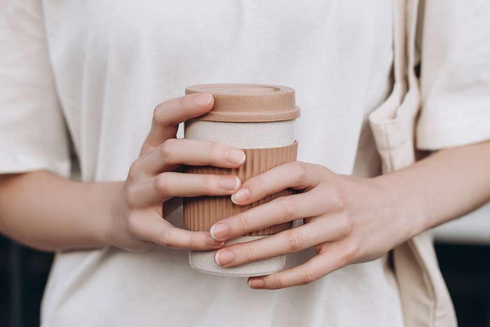 Frau hält Mehrweg-Kaffeebecher
