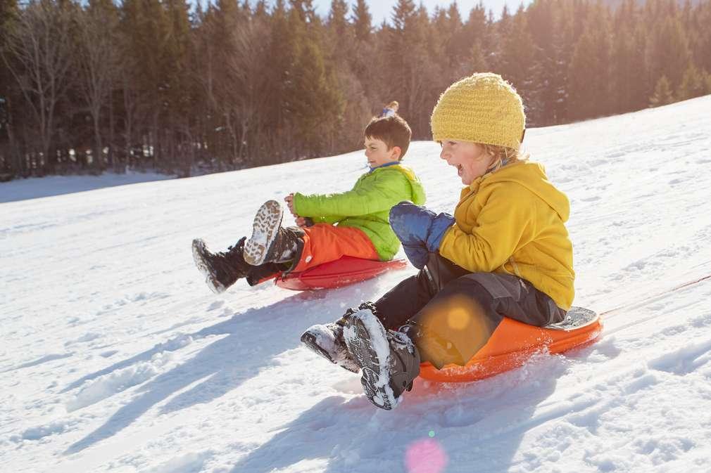 Zwei Kinder rodeln den Berg hinunter