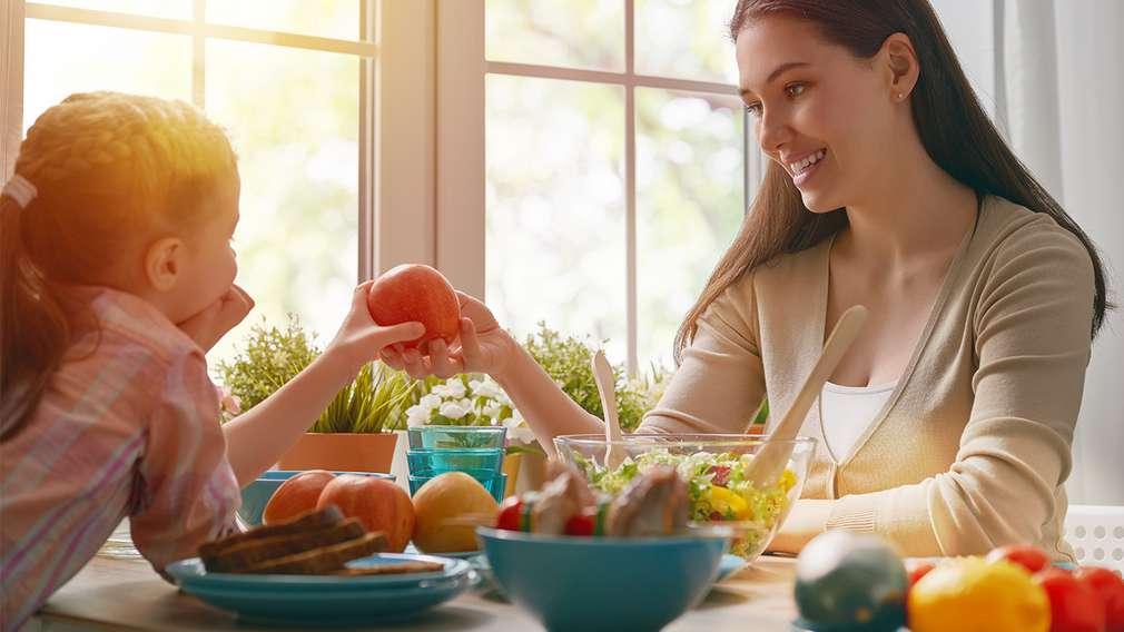 Mutter mit Tochter am Esstisch, gedeckt mit Obst und Gemüse
