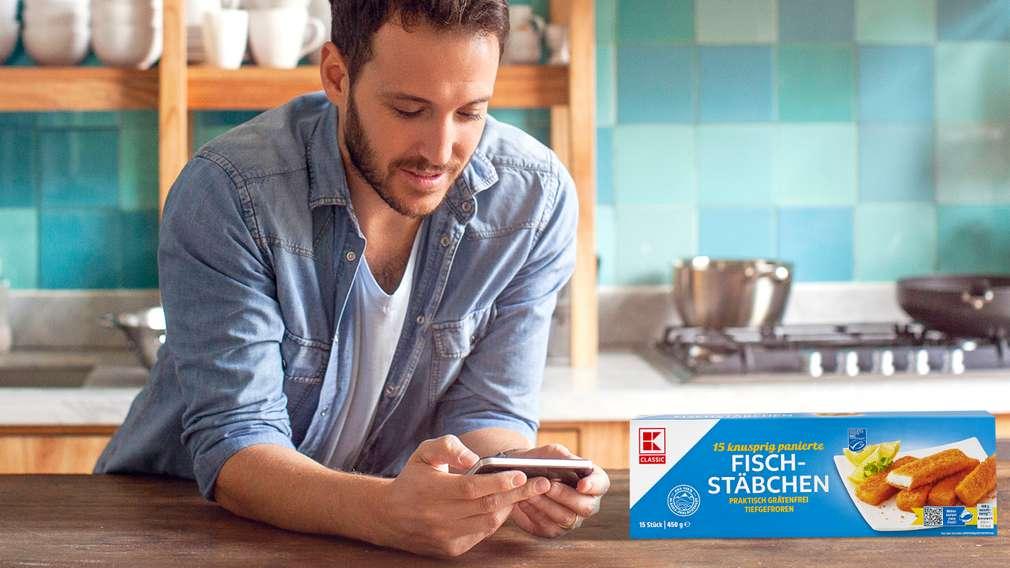 Mann informiert sich am Handy über Herkunft seiner K-Classic Fischstäbchen