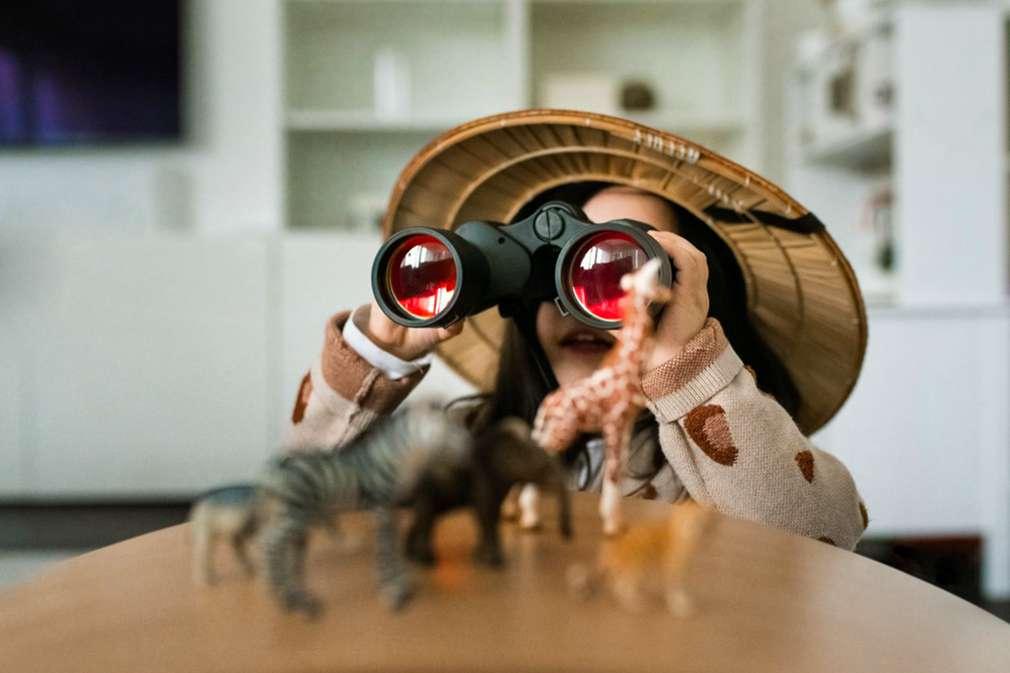 Kind mit Safarihut und Fernglas
