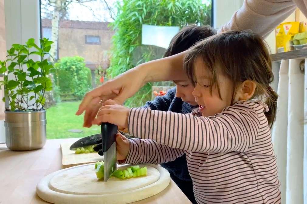 Kinder und Mutter beim Gemüseschneiden