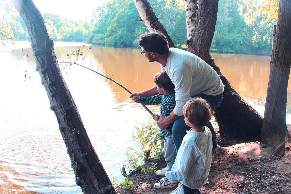 Vater mit Kindern am See