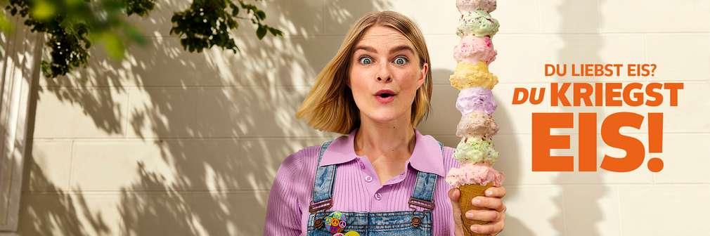 Frau mit Eiswaffel und getürmten Eiskugeln; Schriftzug: Du liebst Eis? Du kriegst Eis!