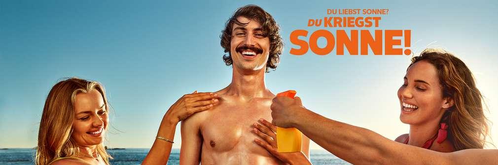 Mann am Strand wird eingecremt; Schriftzug: Du liebst Sonne? Du kriegst Sonne!