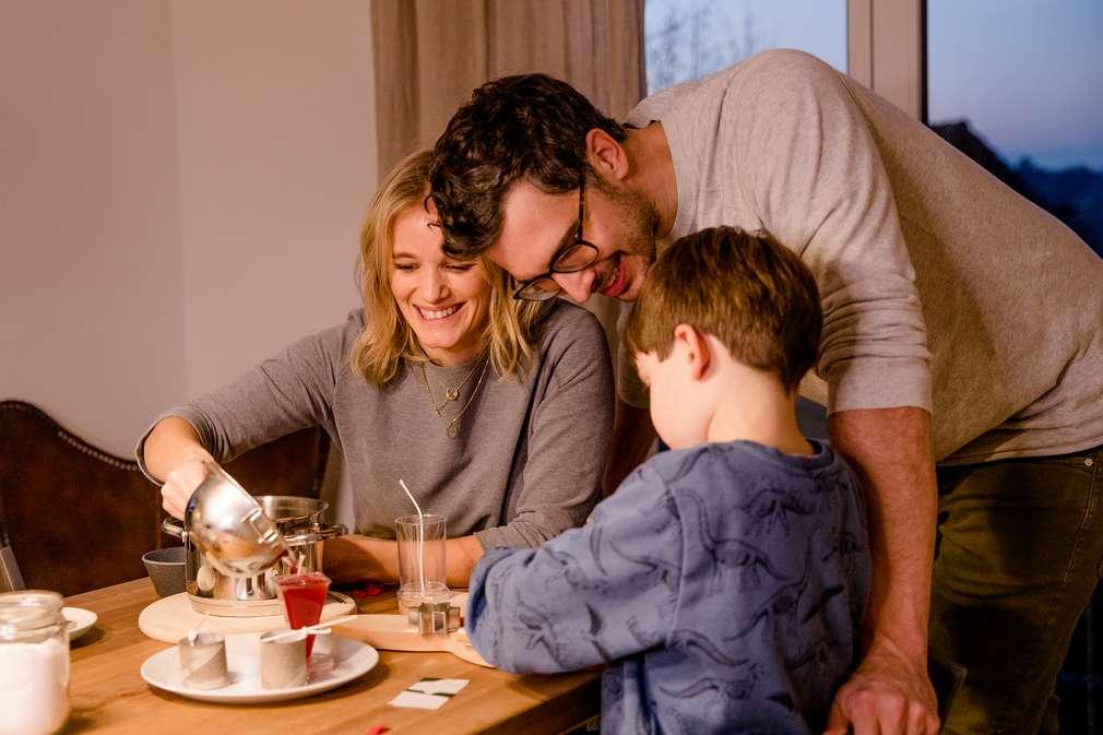 Mutter, Vater und Kind gießen Kerzen