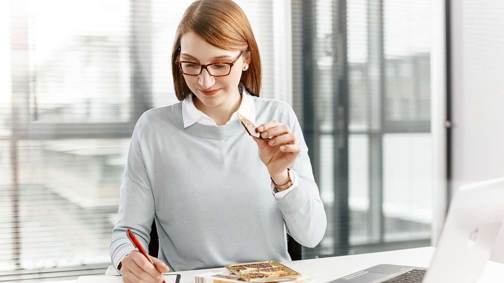 Eine Einkaufsassistentin verkostet Produkte, wie Schokolade.