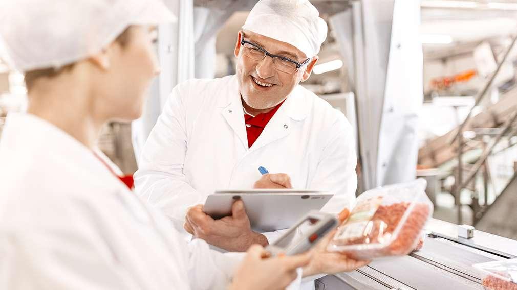 Ein Schichtleiter in der Produktion bespricht die Qualitätssicherung mit einer Mitarbeiterin im Fleischbetrieb.