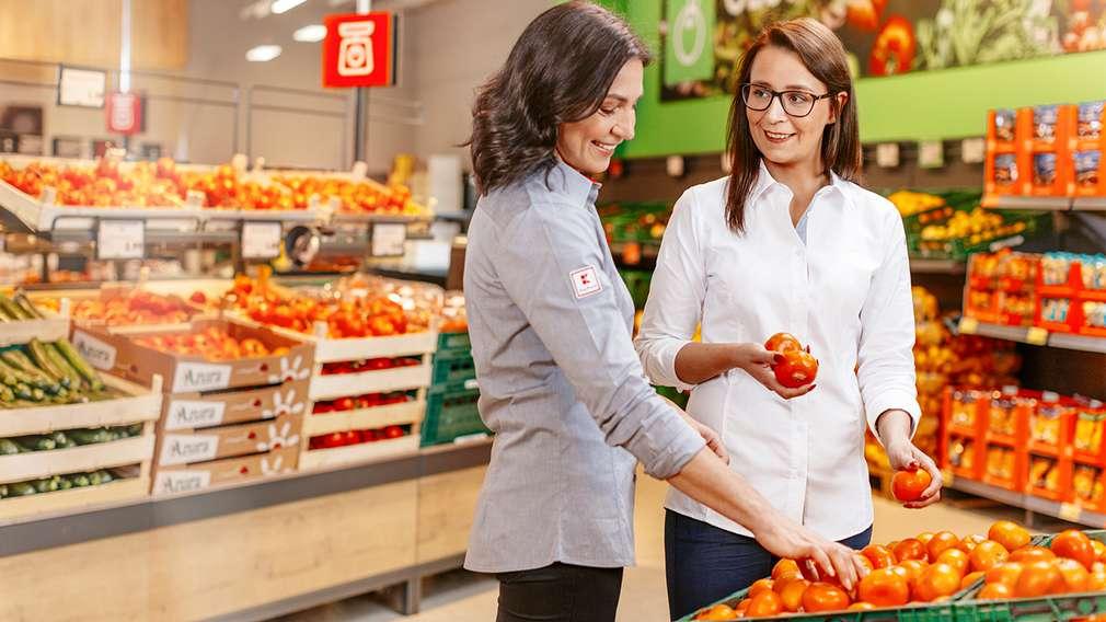 Die Marktleiterin bespricht den Aufbau der Aktionsware in der Obst- und Gemüseabteilung mit der Leiterin des Warenbereichs.