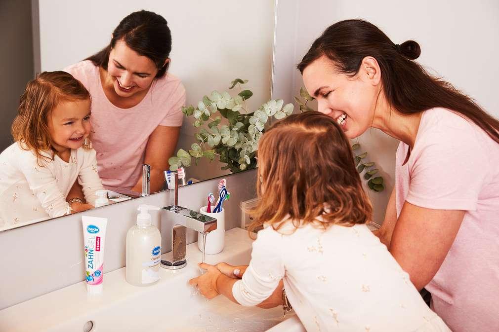 Mutter und Kind waschen Hände
