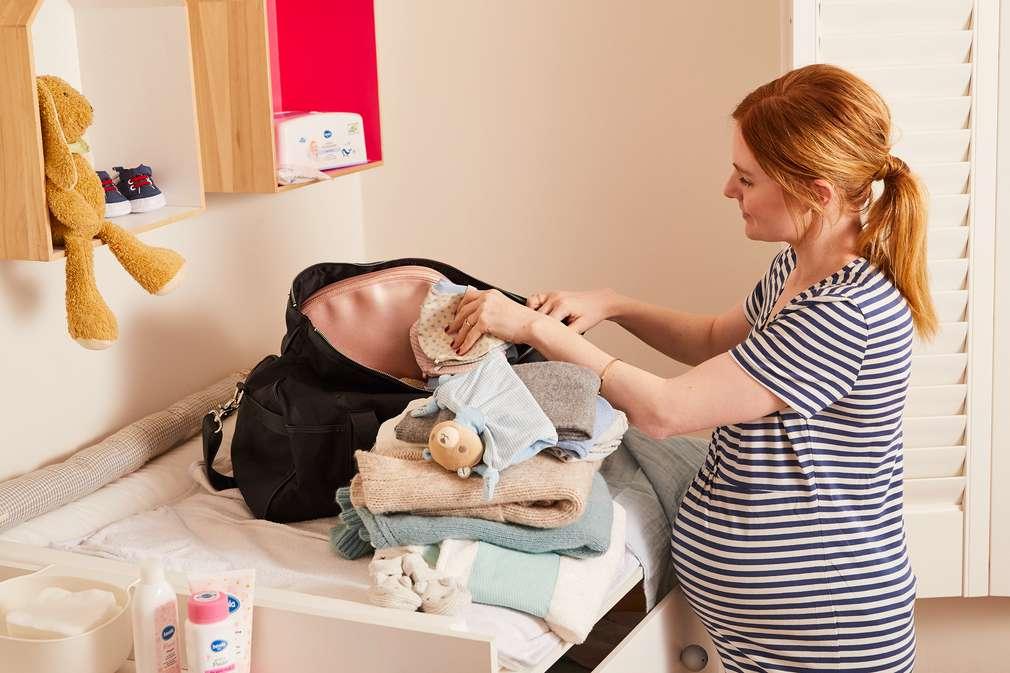 Schwangere Frau packt Tasche
