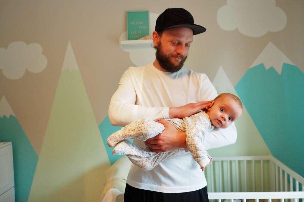 Vater nimmt Baby in den Fliegergriff