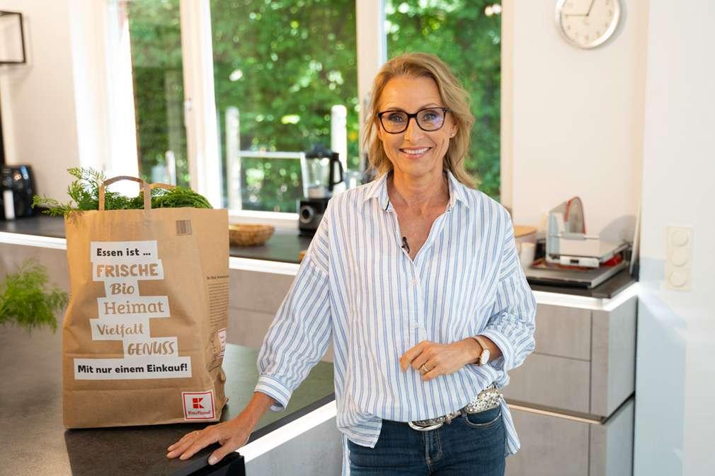 Dr. Alexa Iwan steht an Küchenzeile, darauf steht eine Kaufland-Papiertasche