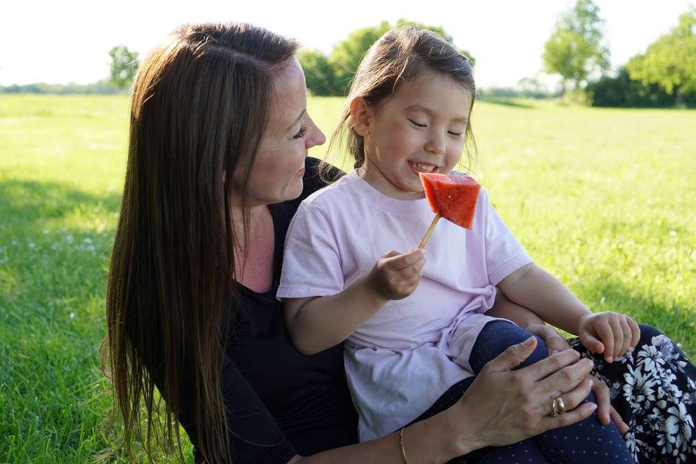 Mutter und Tochter sitzen auf einer Picknickdecke und essen Melone am Stiel