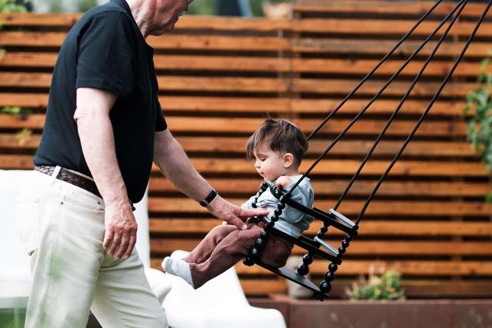 Großvater schubst Kleinkind beim Schaukeln ab