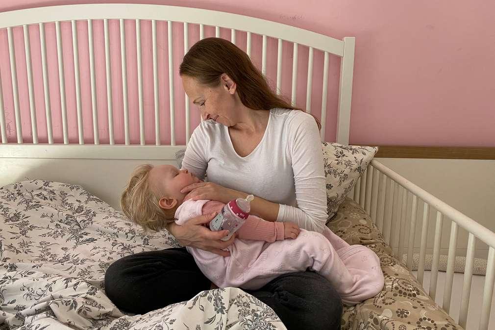 Mutter sitzt mit Baby im Bett