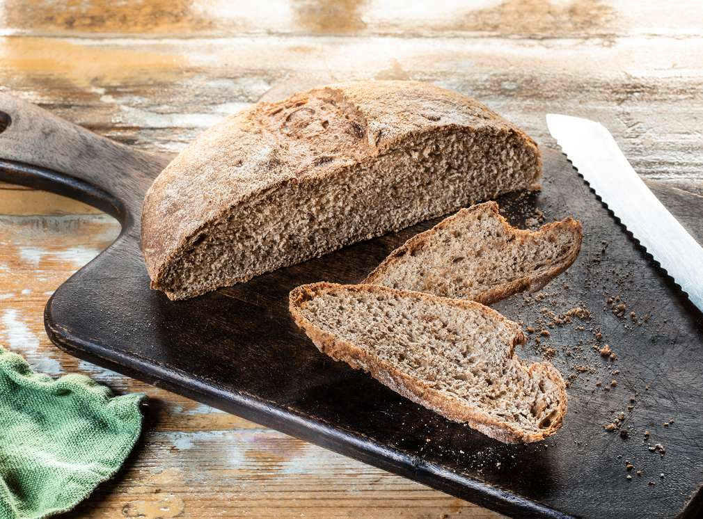 Abbildung aufgeschnittenes Brot auf einem dunklen Brett
