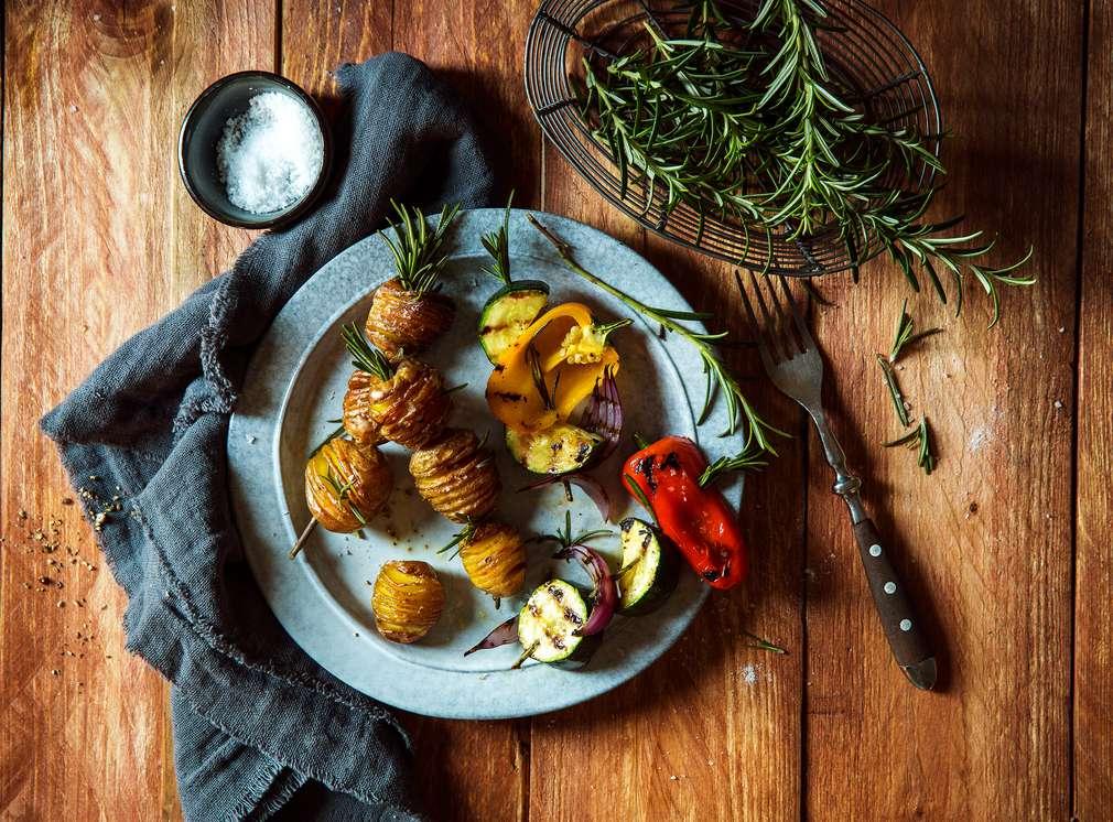 Изображение на картофки, изпечени на барбекю, нанизани на шишчета от розмарин