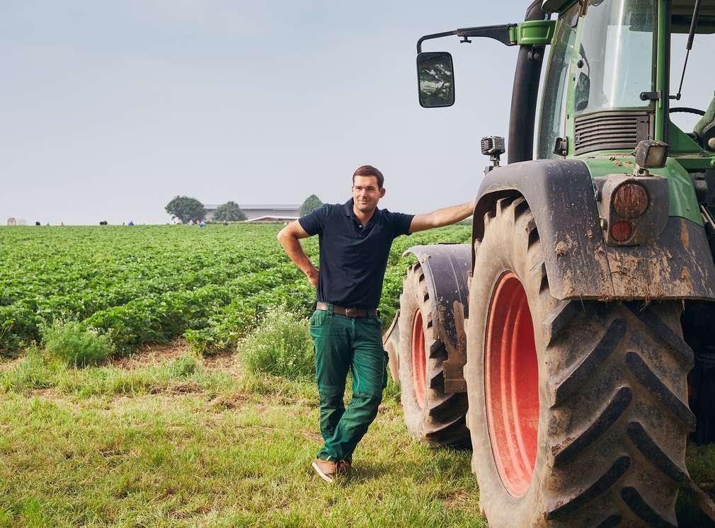 Landwirt auf Feld lehnt an Traktor
