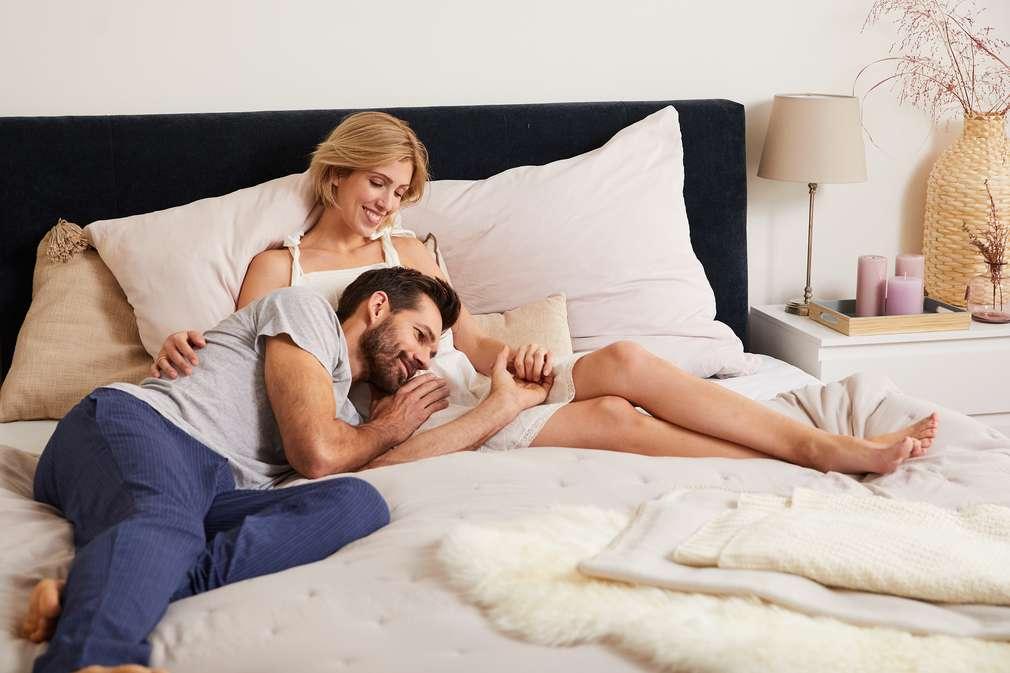 Schwangere Frau und Partner liegen auf dem Bett