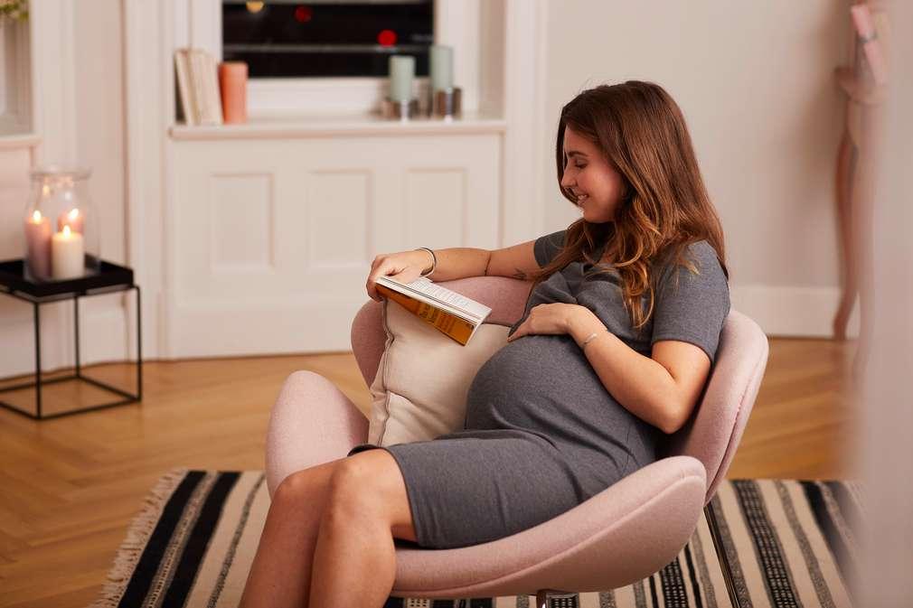 Schwangere Frau sitzt lesend im Sessel