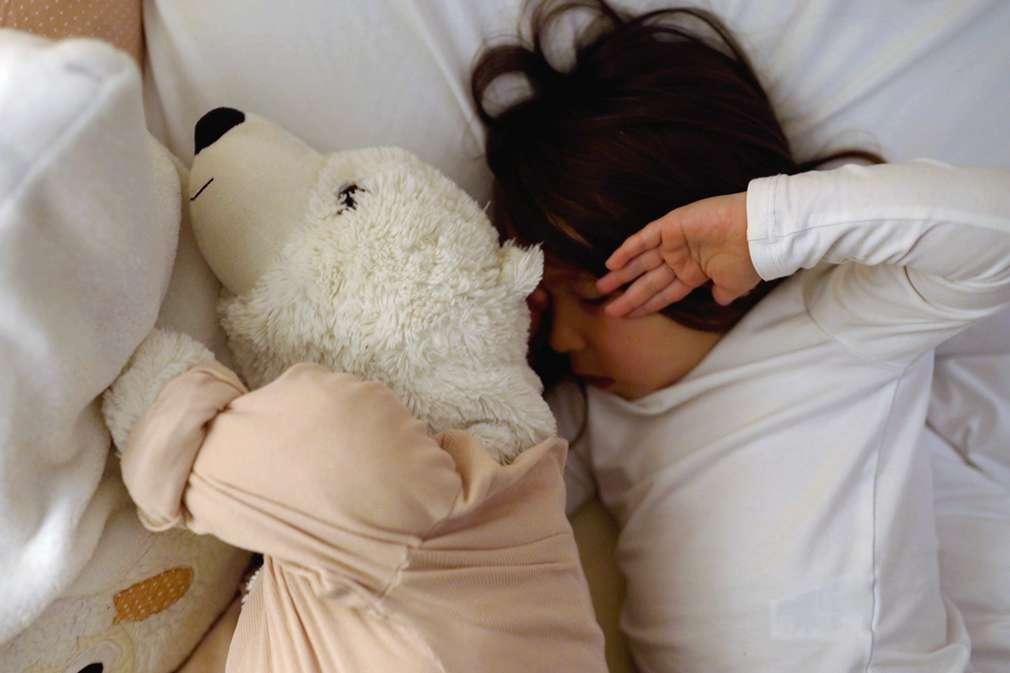 Junge mit Stofftier im Bett
