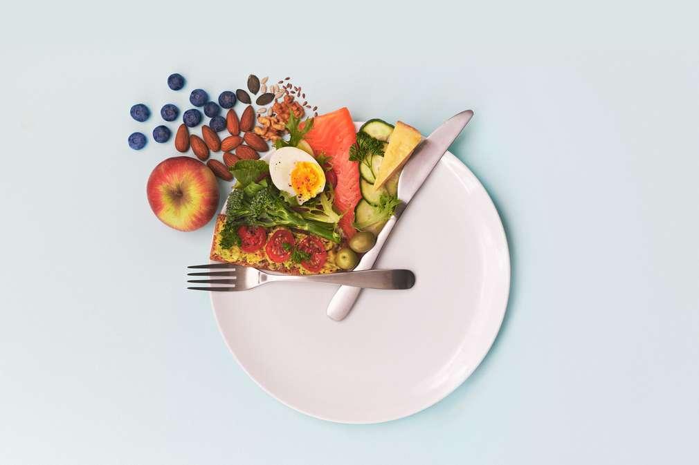 Verschiedene Lebensmittel mit Besteck auf einem Teller angerichtet