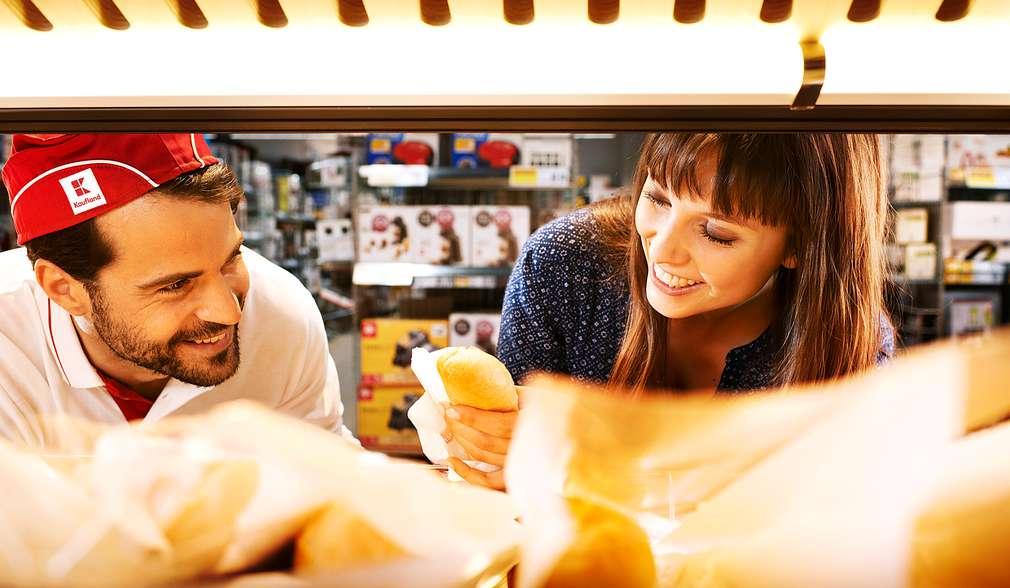 Kaufland-Mitarbeiter und Kundin bei den Backwaren