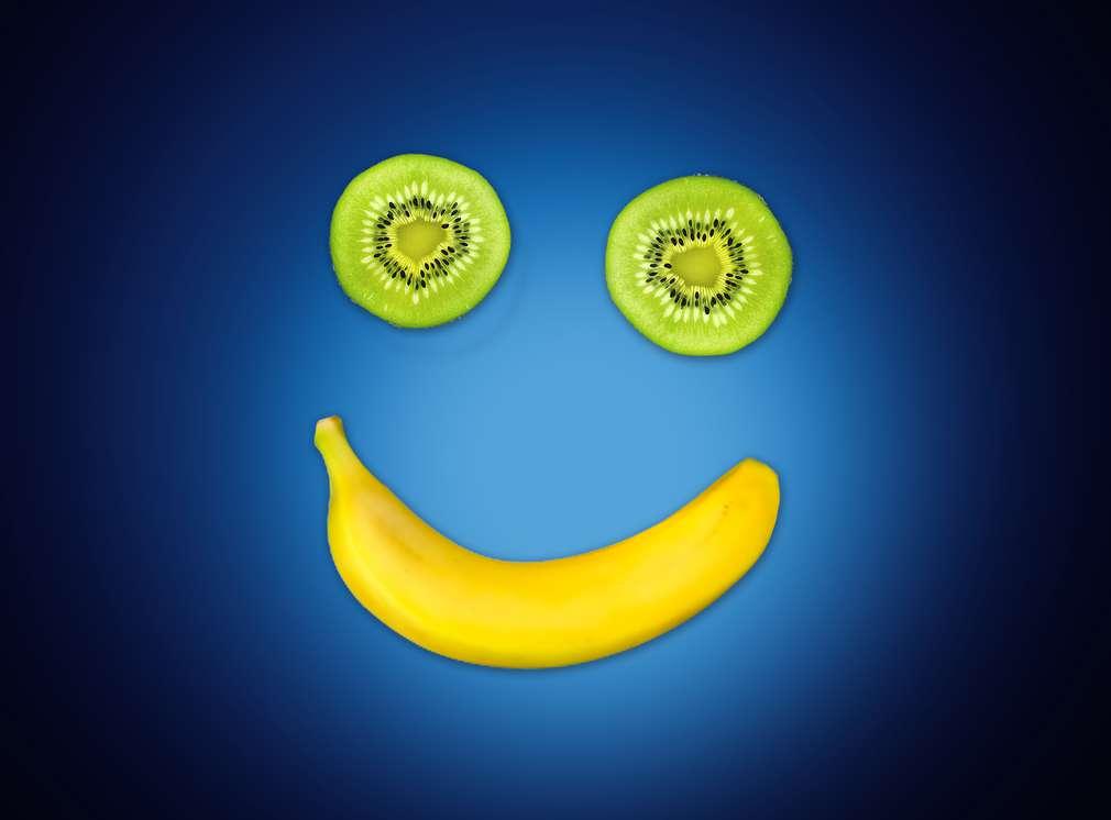 Dva kolieska kivi a banán zobrazujú usmievajúcu sa tvár