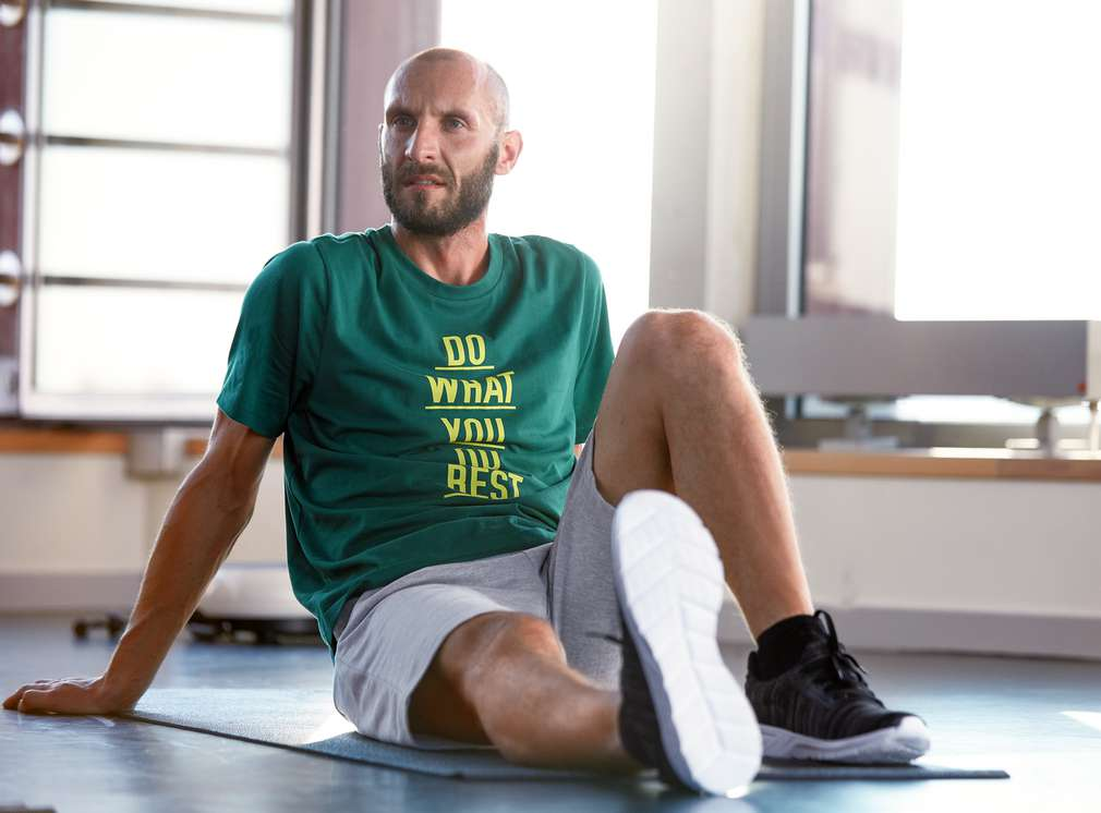 Muž sediaci na karimatke vo fitnes centre robí strečing