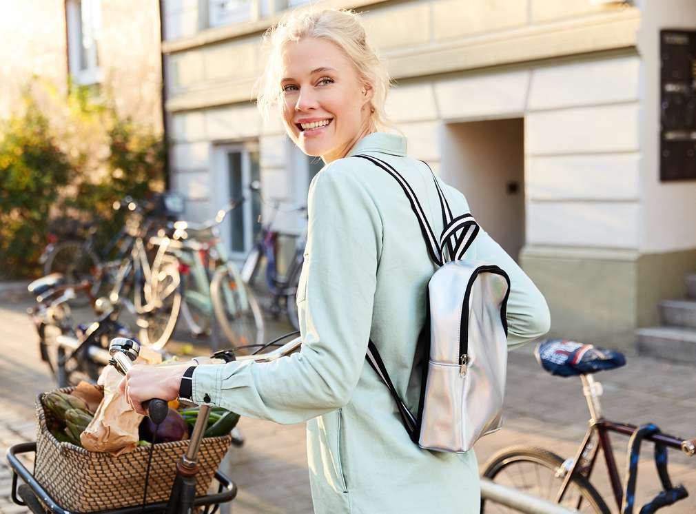 Usmievajúca sa žena drží bicykel