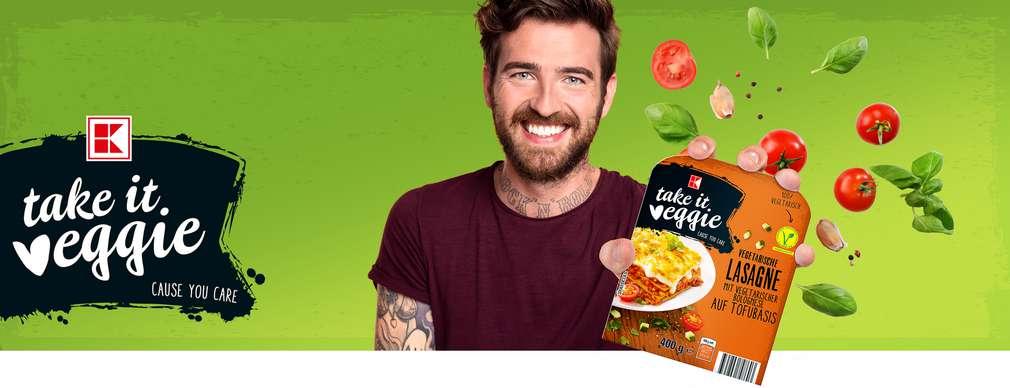 Mladý muž drží v ruke produkt K-take it veggie
