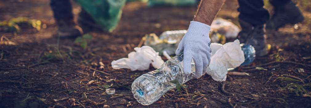 Menschen sammeln Verpackungsmüll aus Plastik auf, der achtlos in die Natur geworfen wurde