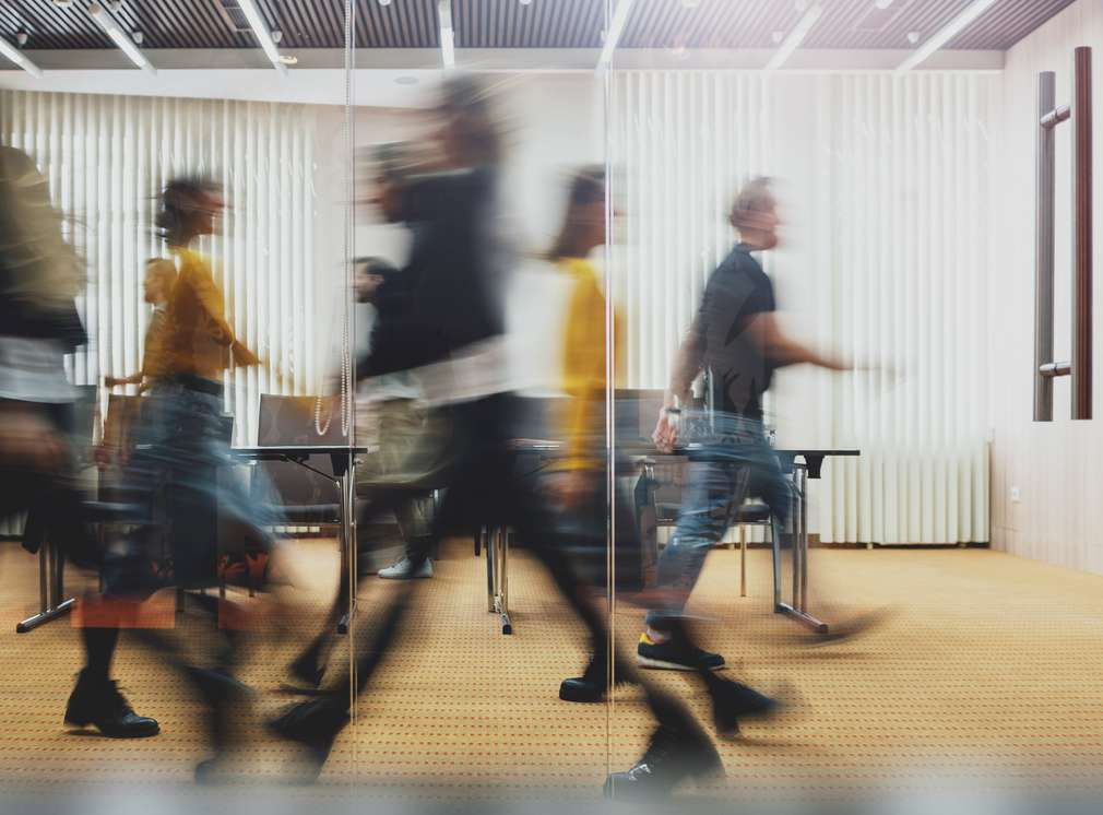 People walk quickly through an office