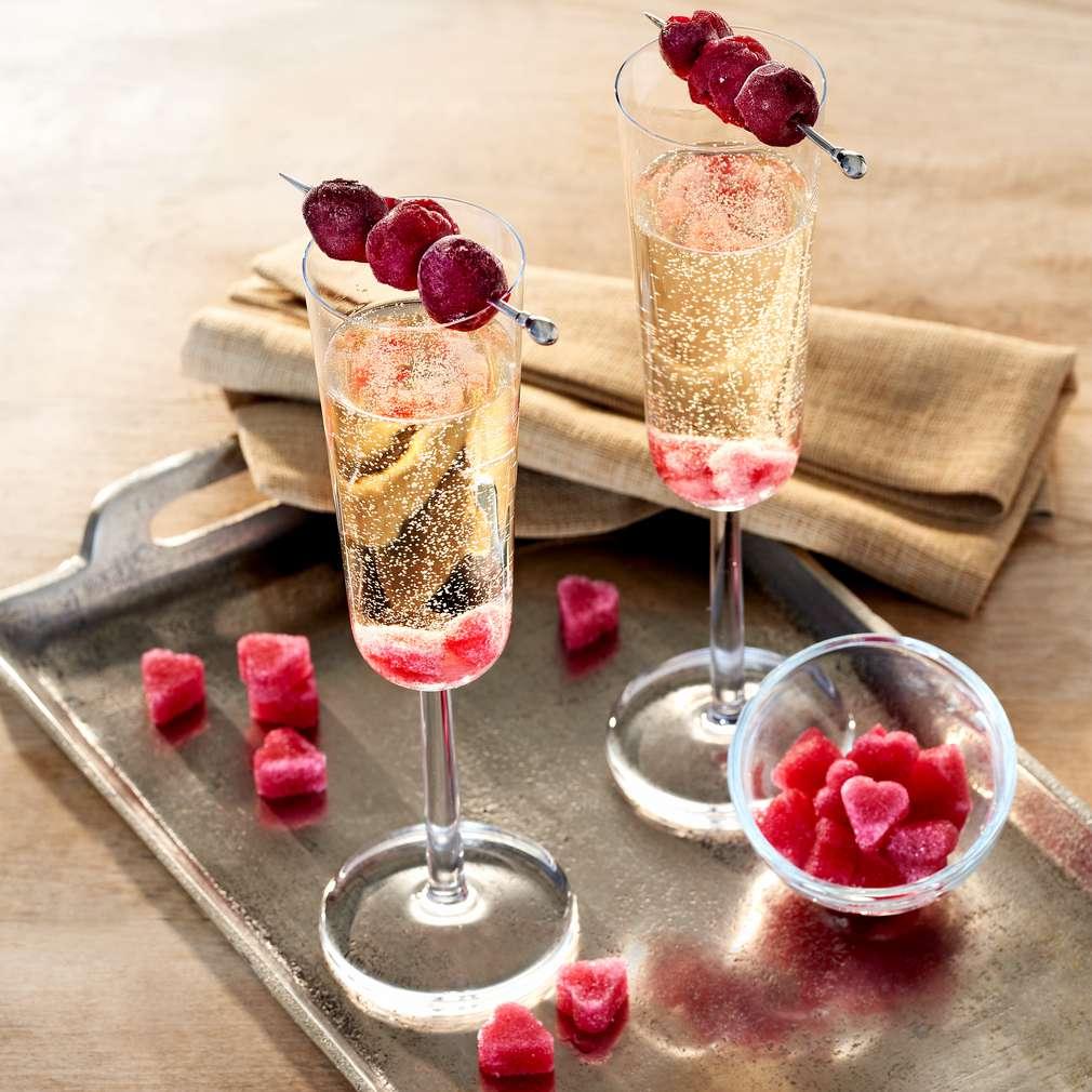 Abbildung des Rezepts Champagner-Aperitif mit Zuckerwürfeln und Kirschenspieß