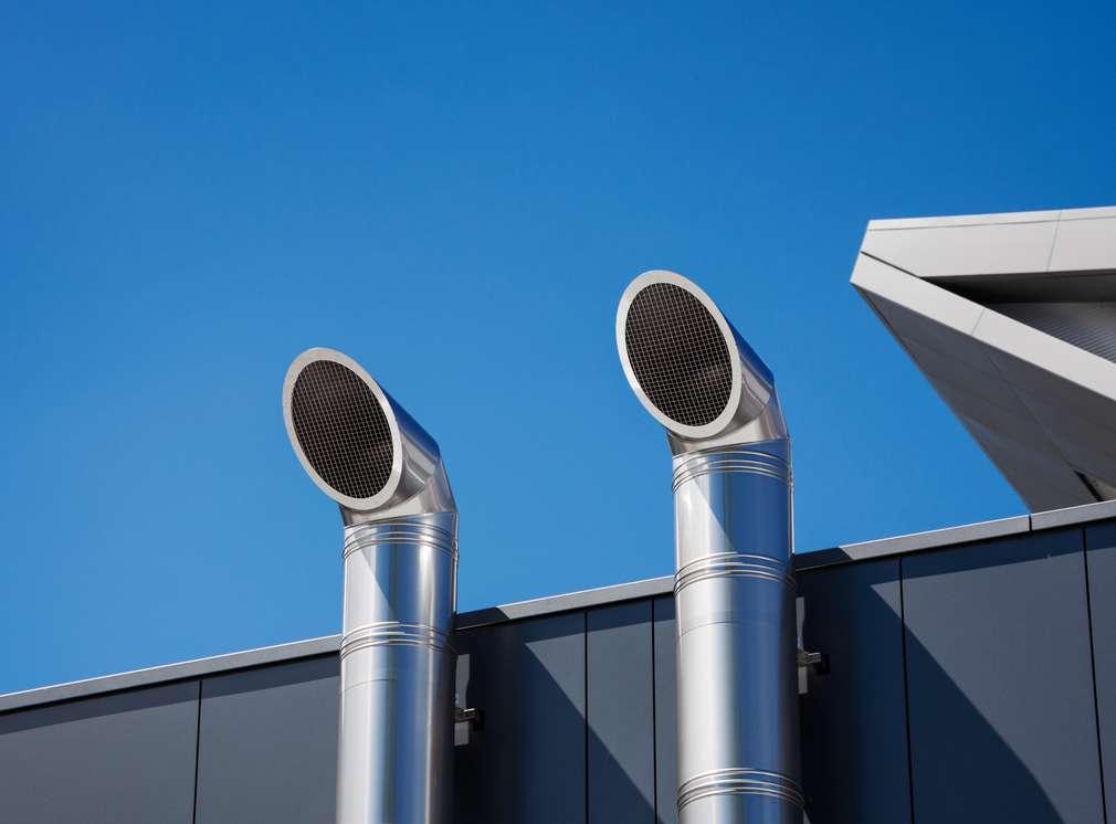 Изображение на две вентилационни тръби, излизащи от покрива на сграда