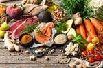 Bunte Vielfalt aus Gemüse, Obst und Fleisch verteilt auf einem dunklen Holztisch